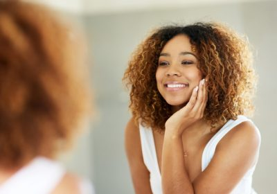 Shot of a smiling woman looking at herself in the mirror.