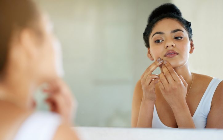 Shot of a young woman inspecting her skin in front of the bathroom mirror.