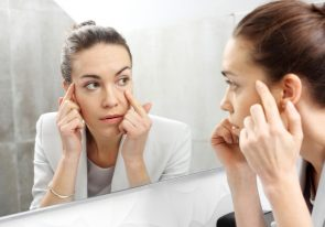 Reflection in the mirror. Woman looks in the mirror noticing her undereye bags