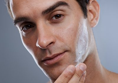 Studio shot of a handsome man applying cream to his face