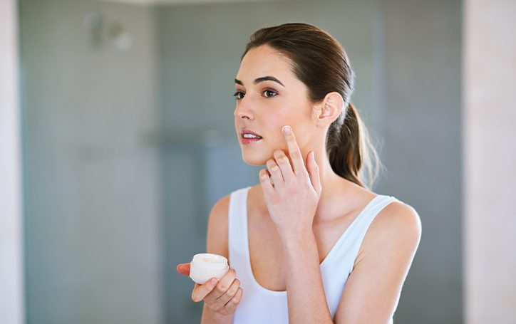 An attractive young woman applying cream to her face.