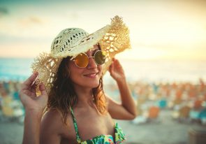 Young woman wearing straw hat ,smiling and enjoying wonderful day at the beach