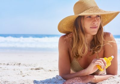 Shot of a woman holding suntan lotion while lying on the beach